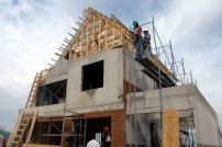 dom w budowie, robotnicy pracuący przy budowie domu